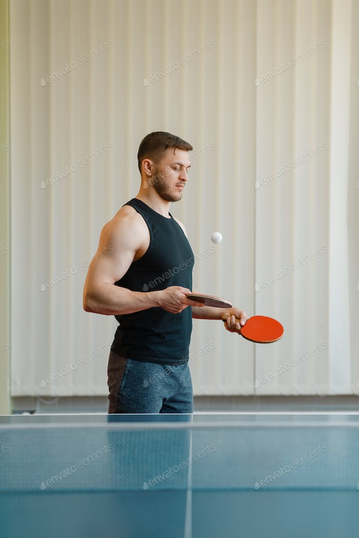 Man with two rackets stuffs blows in ping pong