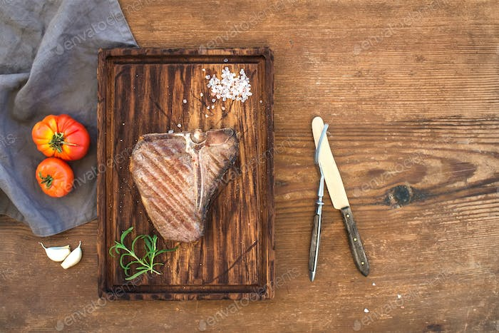 Cooked meat t-bone steak on serving board with garlic cloves