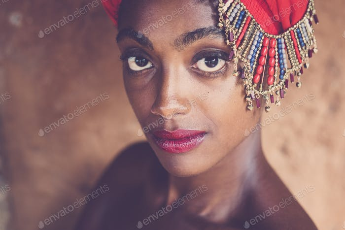 Beauty and beautiful black african girl with traditional fashion hat with jewels posing and looking