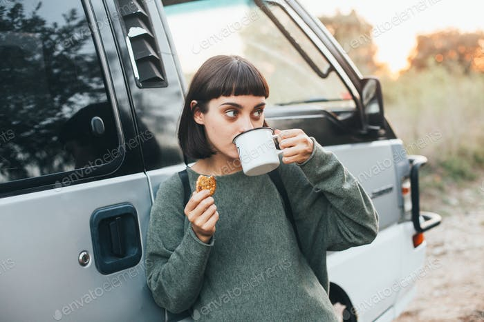 Cute travel woman drink coffee from cup near van