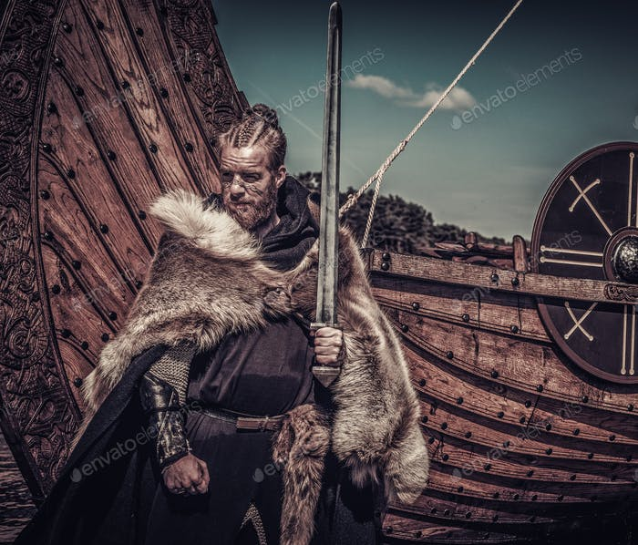 Viking warrior with sword standing near Drakkar on seashore
