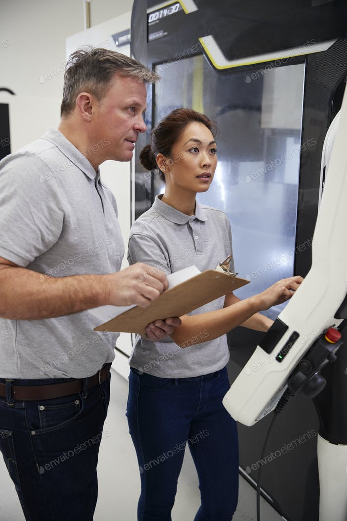 Engineer Training Female Apprentice To Use CNC Machine In Factory