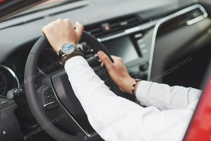 A businessman rides his car, moves on the wheel. A watch on hand in a man's divorce