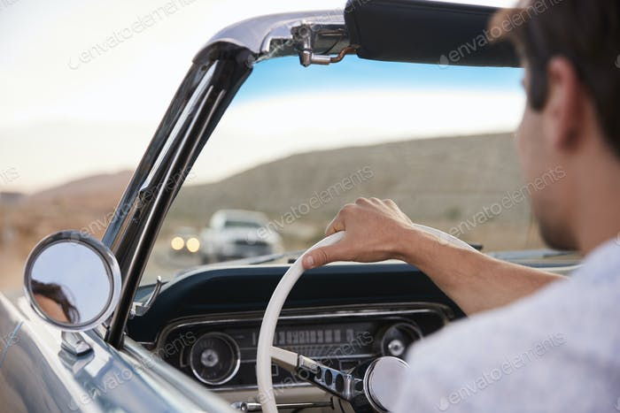 Rear View Of Man On Road Trip Driving Classic Convertible Car Towards Sunset