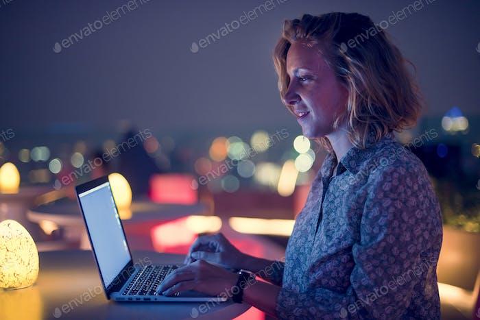 Frau arbeitet an einem Laptop in einer Bar auf dem Dach