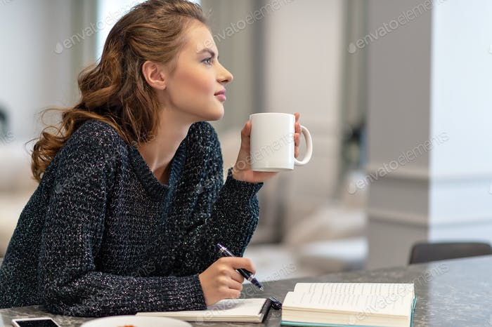 Woman sitting on the table  and writing something in her noteboo