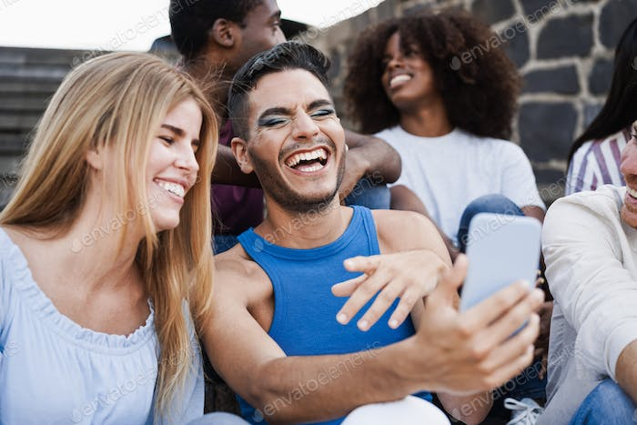 Young diverse people using mobile phones outdoor in the city