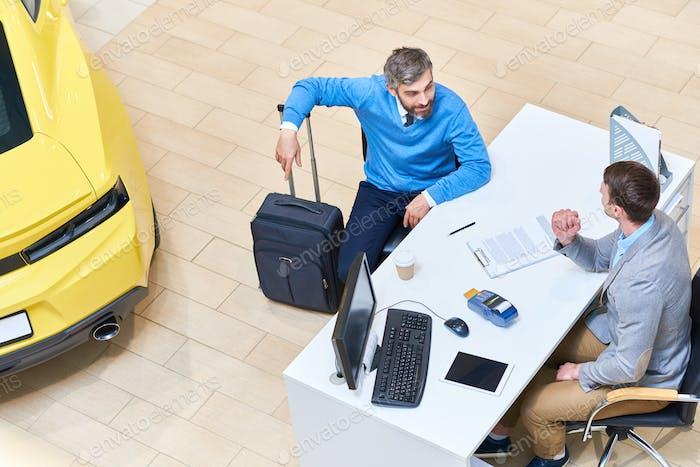 Mature Man Renting Car in Showroom