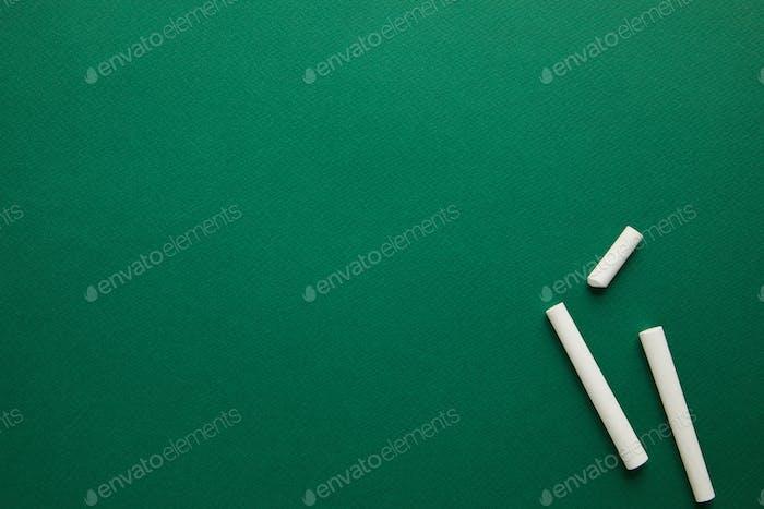 Draufsicht auf weiße Kreiden auf grüner Tafel