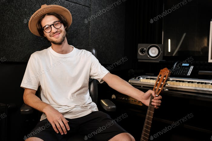 Young stylish musician happily looking in camera in studio