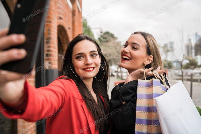 Zwei junge Freunde nehmen ein Selfie mit Handy.