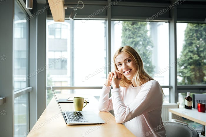 Happy lady sitting in office coworking while using laptop