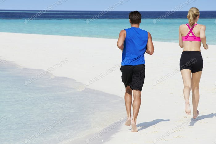 Rear View Of Couple Running On Beautiful Beach