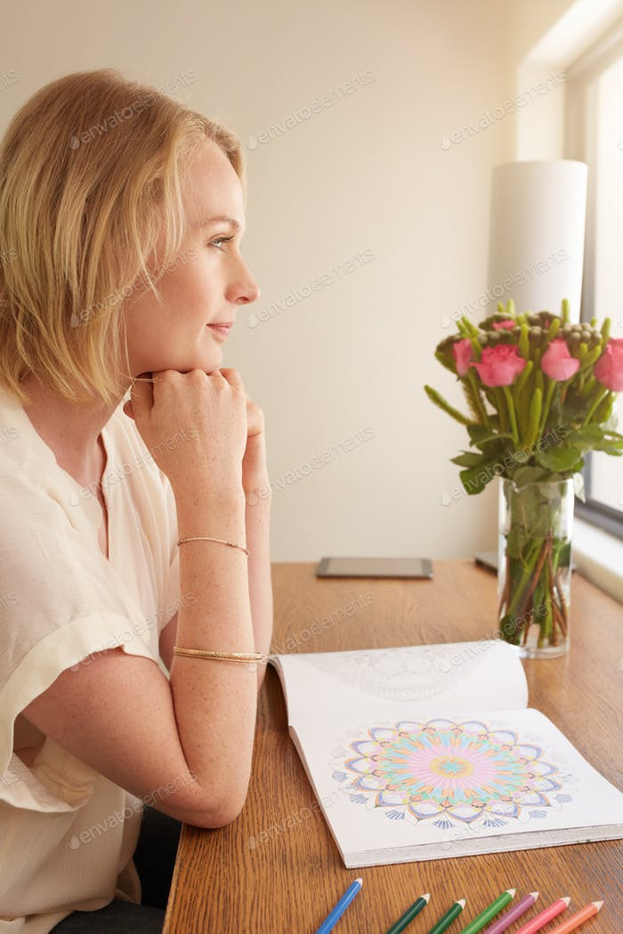 Thoughtful woman at a table with adult coloring book