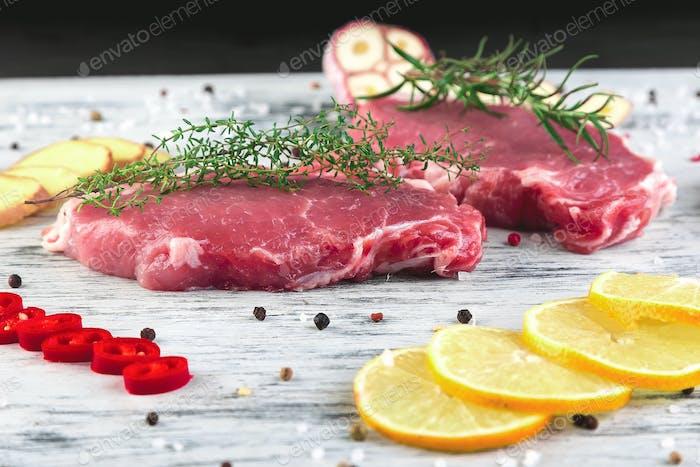 Rohes Schweinefleisch auf schwarzem Schieferplatte mit Gewürzzutat