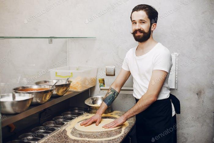 Chef in the kitchen prepares pizza