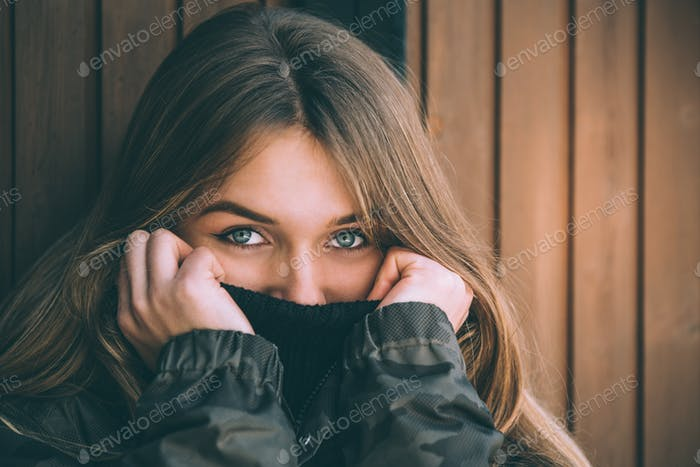 portrait Young pretty woman in winter in the snow in a log cabin wooden