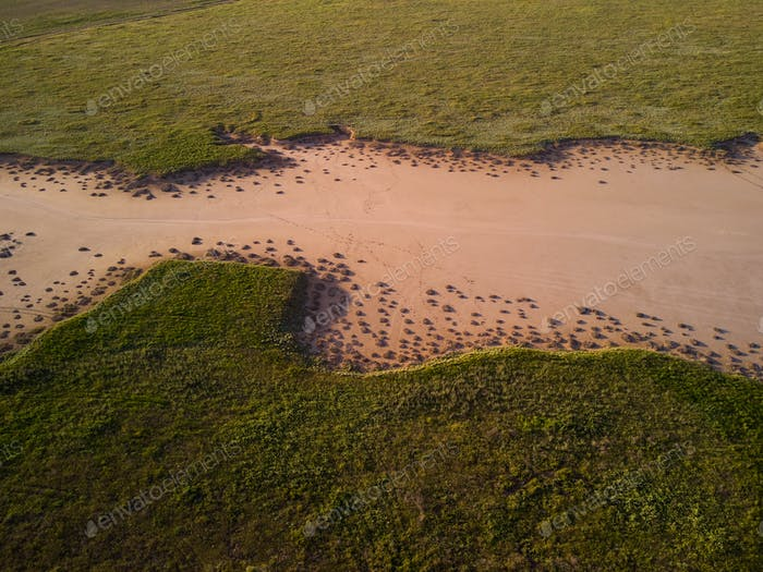 aerial view of green grass around a sandy ravine formed by rain