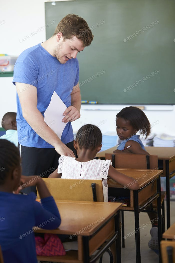 White male teacher helping schoolgirls at elementary school