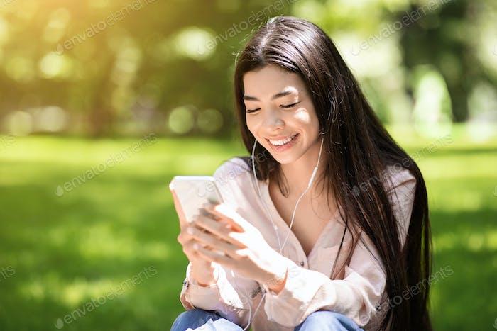 Lieblings-Freizeit. Happy Asian Girl Hören Musik im Freien Mit Smartphone Und Ohrhörer