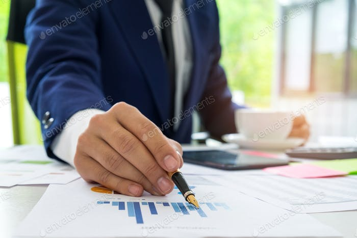 Businessman uses a pen pointing at the chart to analyze the data