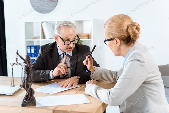 mature lawyers discussing contract in office
