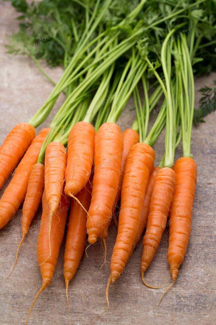 Frische und süße Karotte auf einem grauen Holztisch.