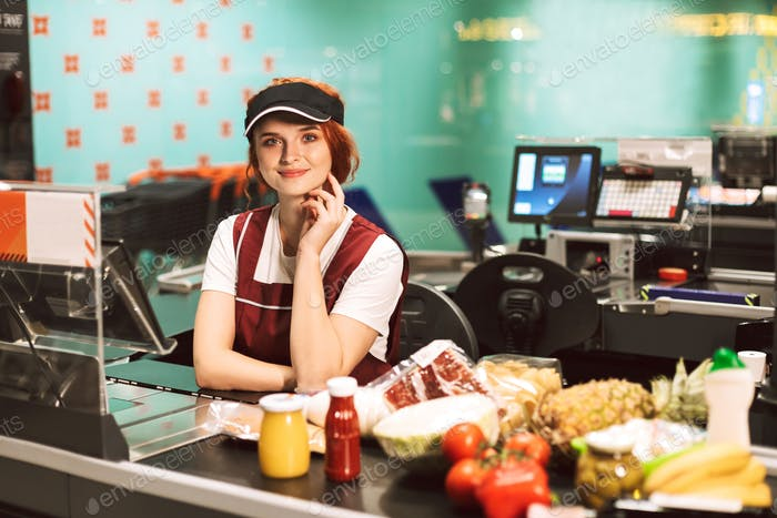 Young smiling female cashier in uniform dreamily looking in came