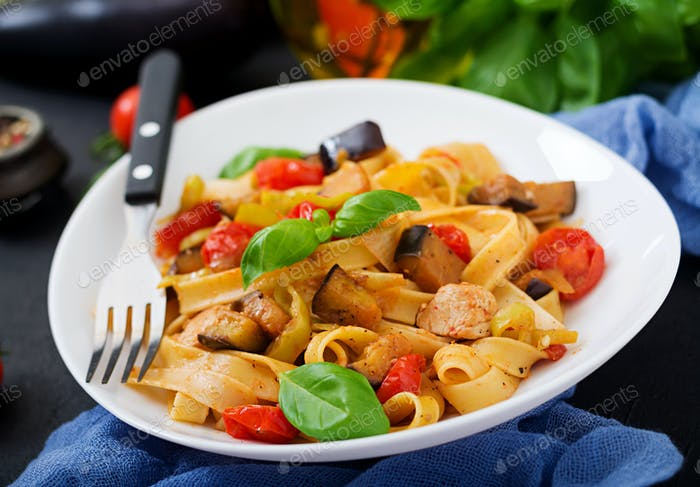 Pasta Fettuccine with tomato, eggplant and chicken fillet in bowl.