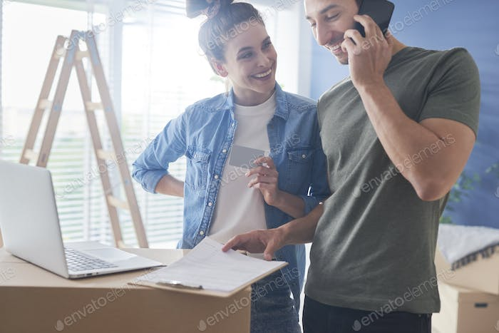 Couple making a call and using credit card