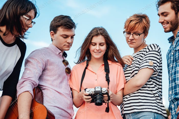 Fünf Freunde in einem halben Kreis, lächelnd, Blick auf die Kamera in den Händen des Mädchens