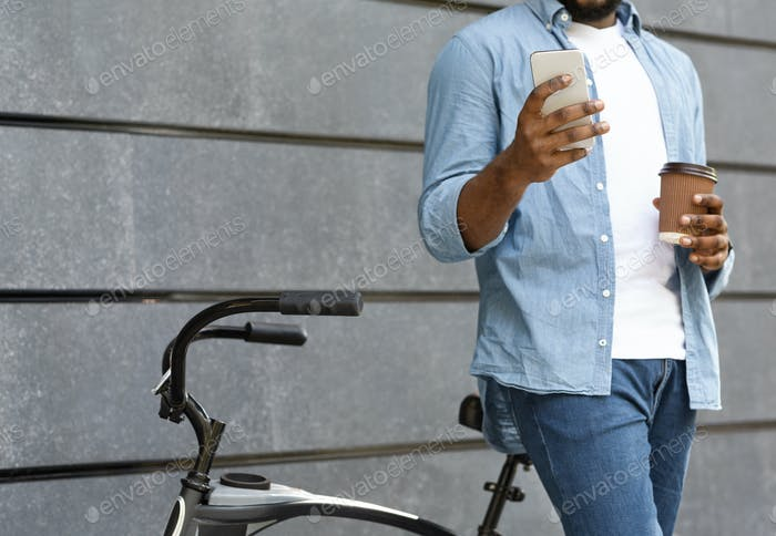 Unrecognizable man with bicycle using smartphone and drinking coffee outdoors