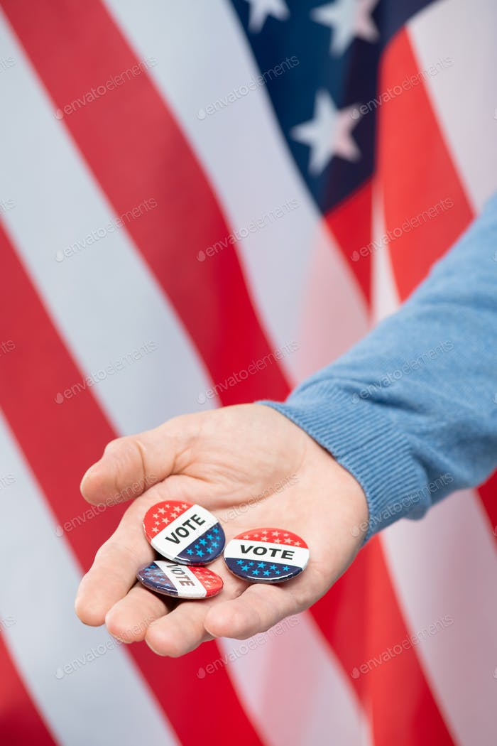 Hand of young contemporary manager or businessman showing vote insignias