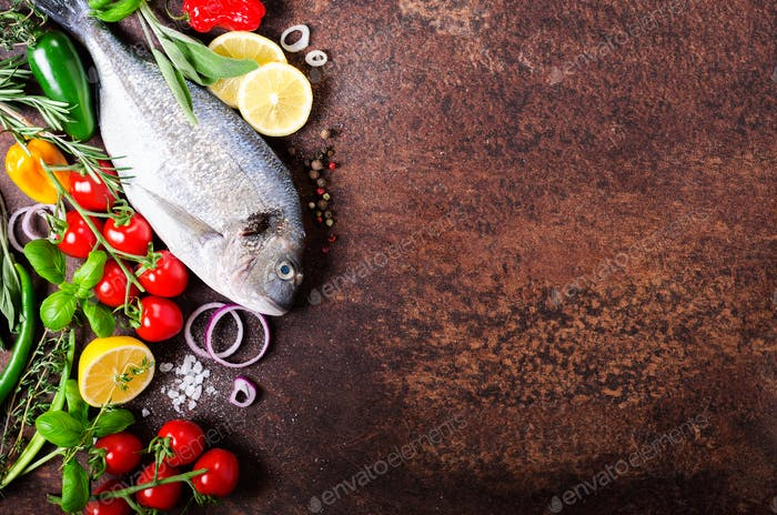 Fresh uncooked fish, dorado, sea bream with lemon, herbs, vegetables and spices on rustic background
