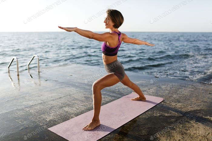Young lady in sporty top and shorts practicing yoga with sea on background
