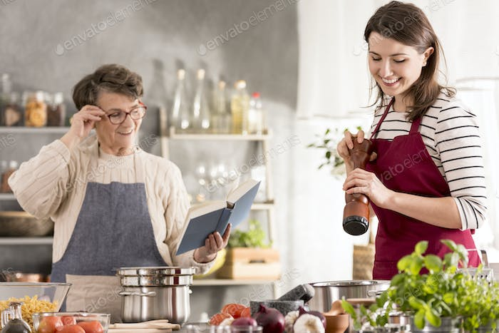 Grandmother reading recipe from cookbook