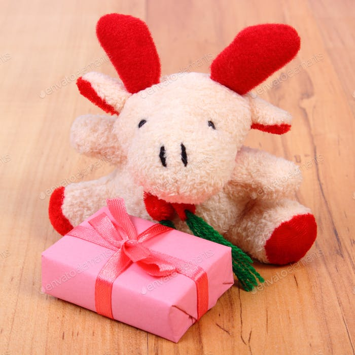 Plush reindeer with gift for Christmas or other celebration
