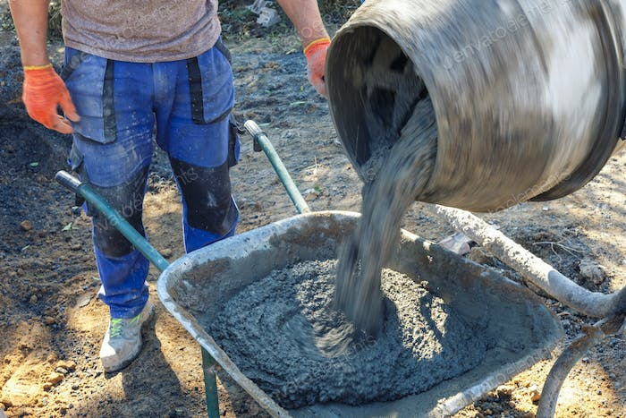 Builder pouring cement from a cement mixer