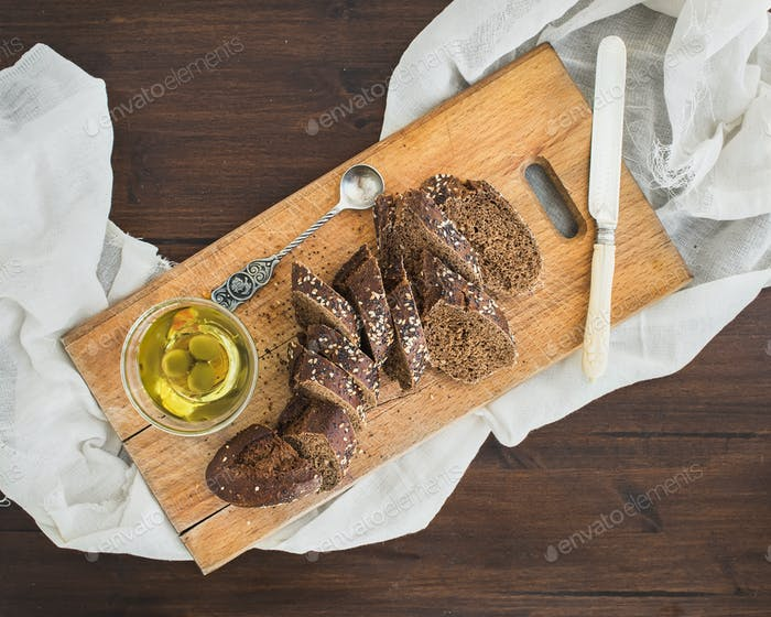 Dark baguette cut in slices with olive oil on a rustic wooden bo