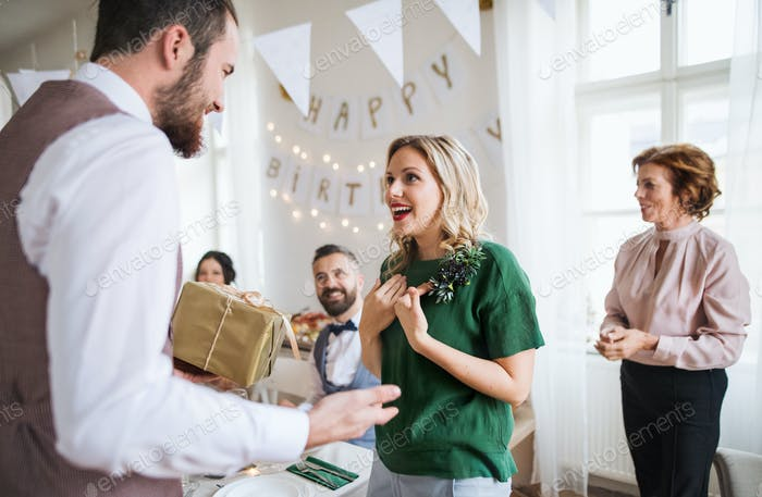 A man giving gift to a young surprised woman on a family birthday party.