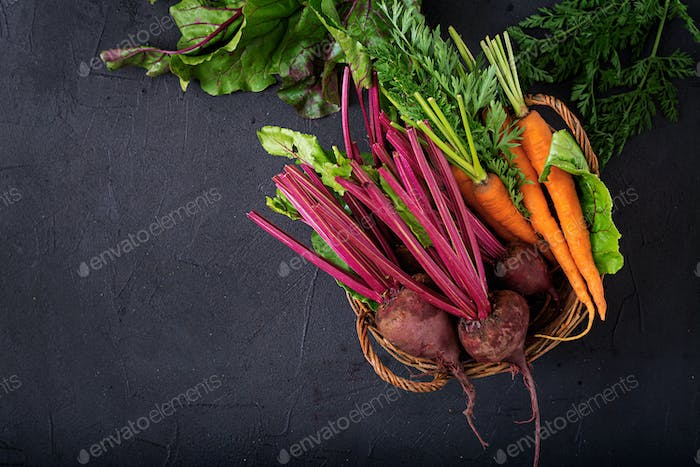 Young beetroot and carrots with a tops in a basket on a dark background. Flat lay. Top view