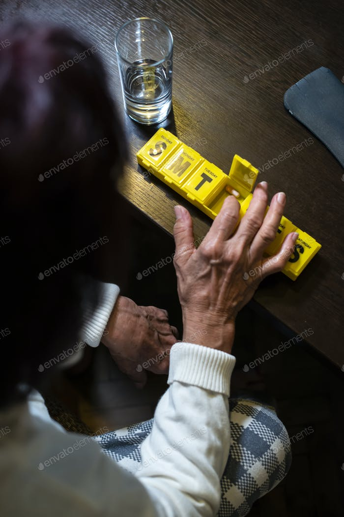 Senior woman take pills from box. Healthcare and old age concept