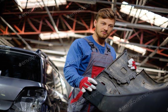 Mechaniker mit Autostoßstange in einer Werkstatt