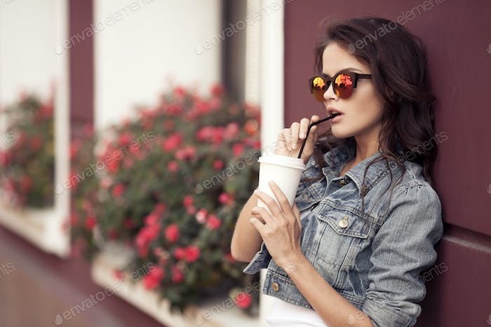 Young Woman Drinking Coffee From Paper Cup On A City Street