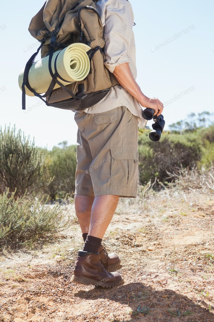 Hiker holding his binoculars on country trail on a sunny day