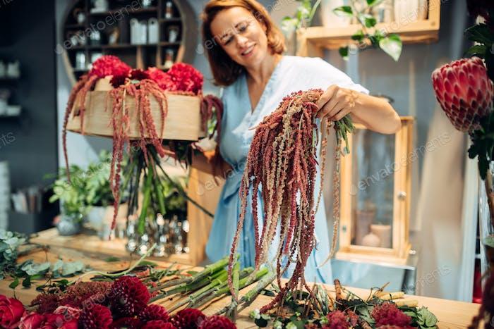 Florist decorates flower bouquet in shop closeup