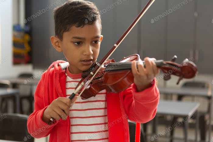 Front view of cute mixed-race schoolboy playing violin in classroom at elementary school