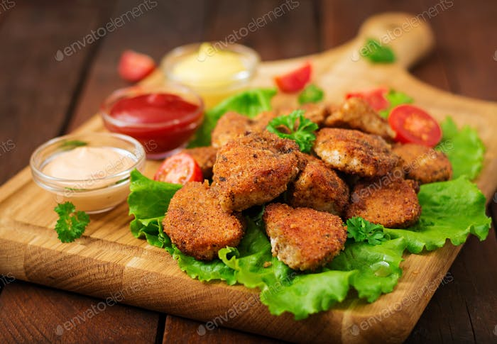 Chicken nuggets and sauce on a wooden background.