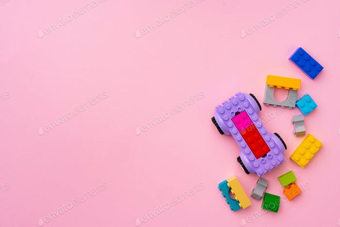Plastic constructor details on pink background close up