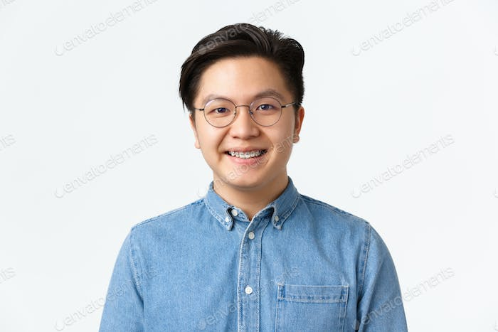 Close-up of hopeful cute asian guy with braces smiling at camera, satisfied with professional dental